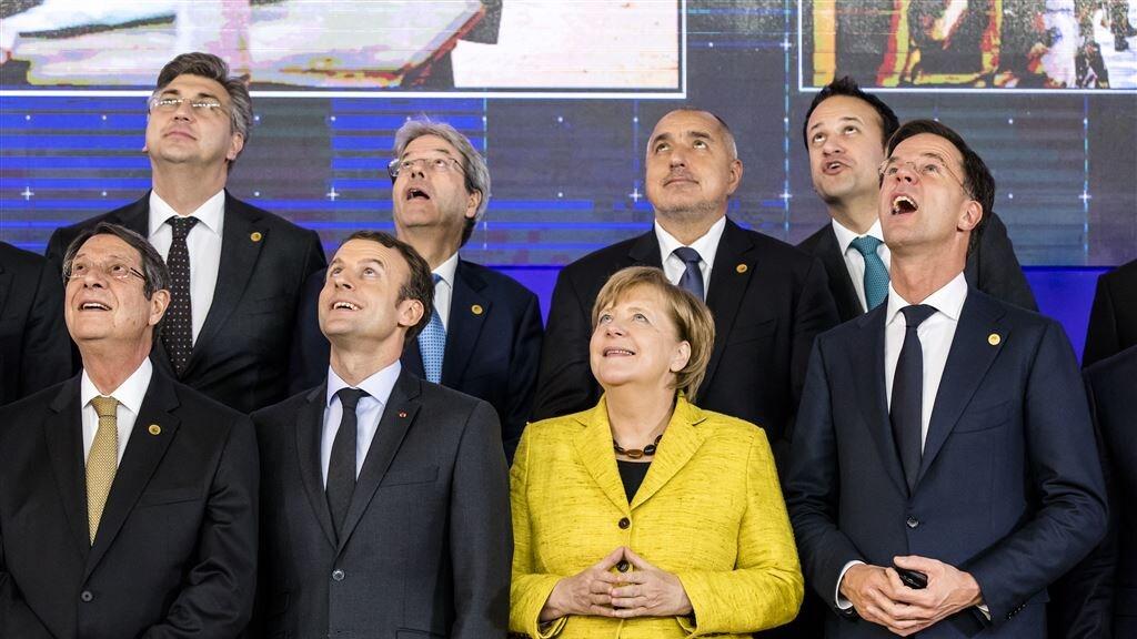 De Franse president Macron, de Duitse Bondskanselier Merkel en premier Rutte kijken naar een drone in de lucht tijdens de Europese Raad van december 2017 in Brussel.