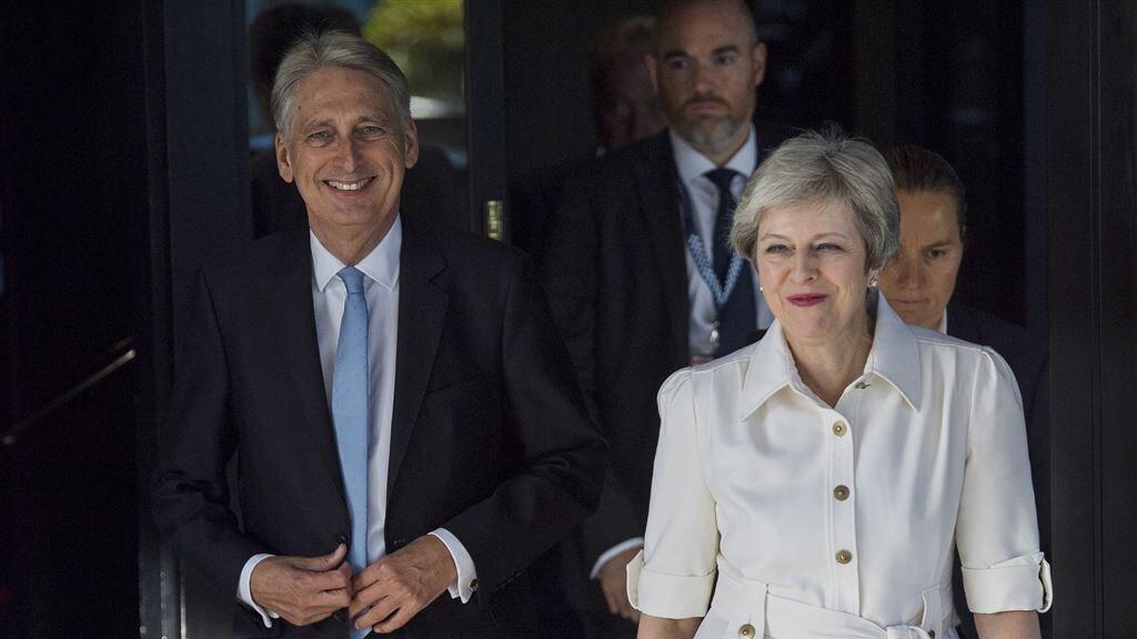 De Britse minister van Financiën Philip Hammond en premier Theresa May op weg naar het partijcongres.