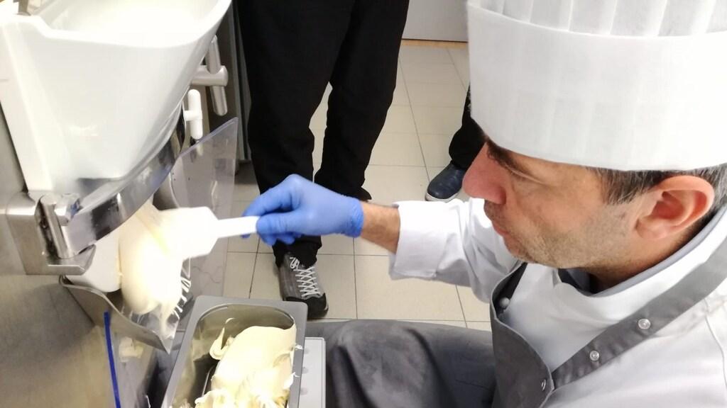 Tijdens de wedstrijd, volledig geconcentreerd, schept Roberto het vanille-ijs in een bak.