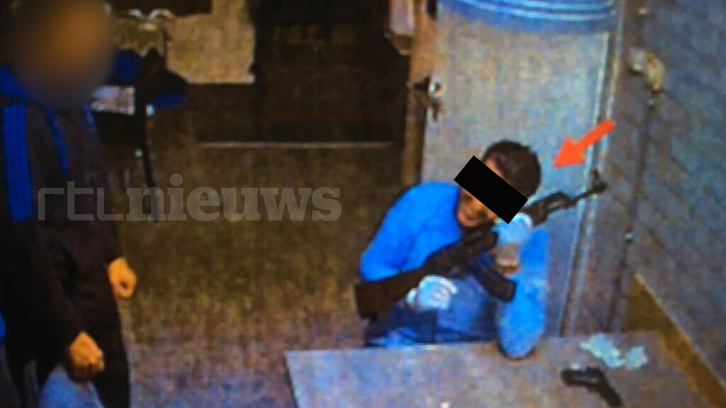Een verdachte legt zijn wang liefkozend tegen de AK-47. Hij heeft daarbij een brede grijns op zijn gezicht.