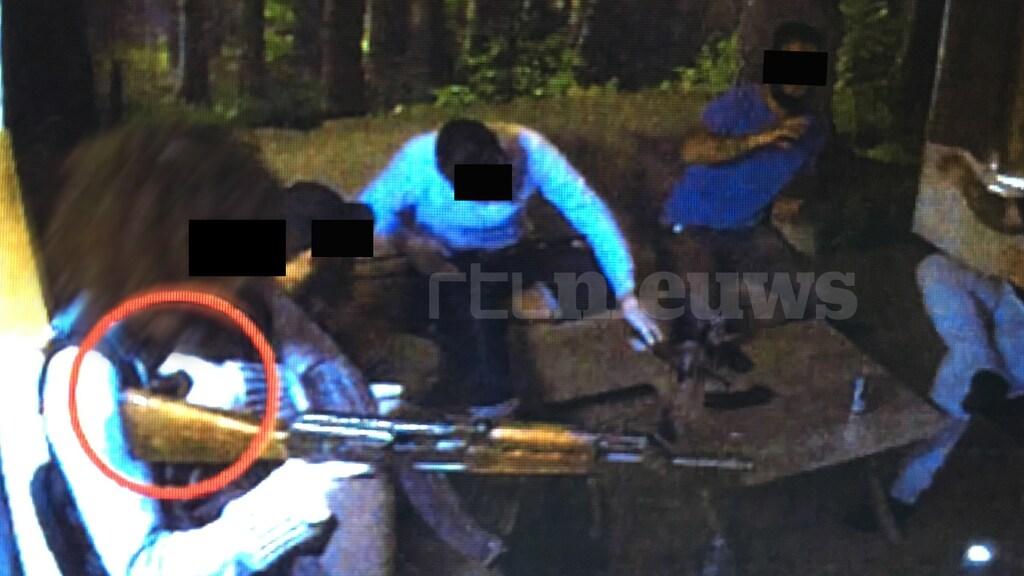 Een verdachte richt zijn kalsjnikov en houdt zijn linkerhand op de ontsteking van zijn bomvest.