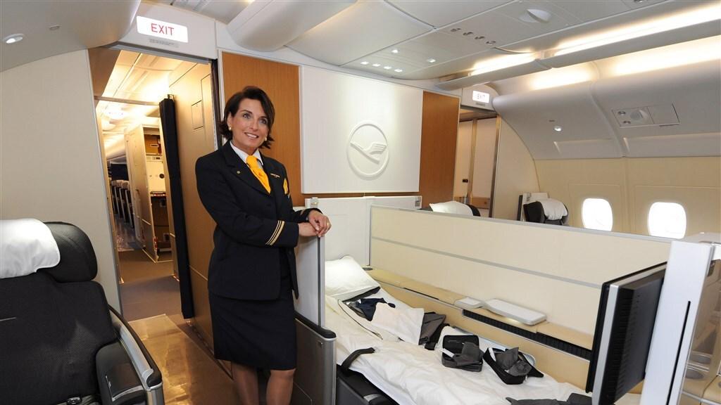 Een stewardess van Lufthansa toont een first class bed in een A380.