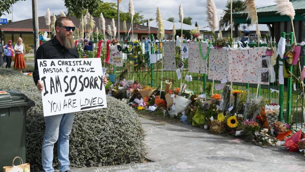 Een man staat voor een moskee in Hastings, Nieuw-Zeeland