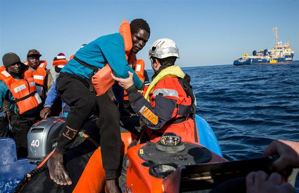 Een medewerker van Sea-Watch helpt een migrant aan boord van een bootje. (Archieffoto.)