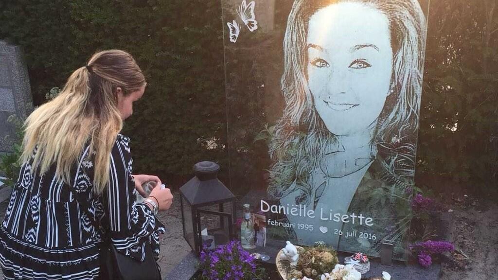 Het graf van Daniëlle, de andere dochter van Nicolette steekt een kaarsje aan.