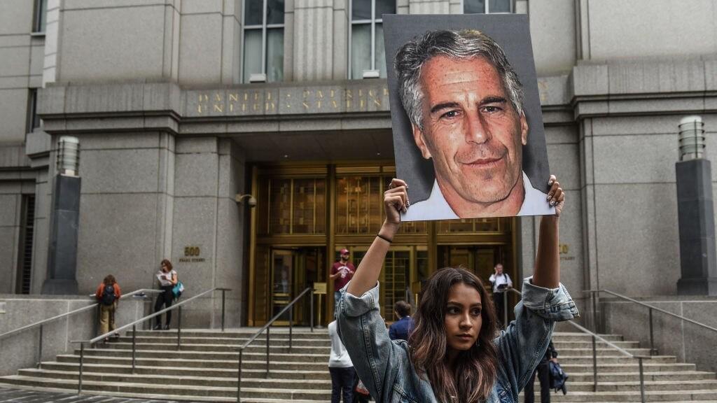 Een vrouw bij de rechtbank met een foto van Jeffrey Epstein.