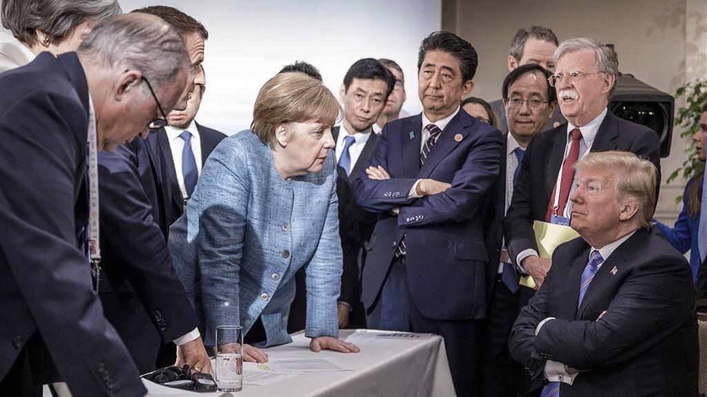 De iconische foto van de Duitse fotograaf Jesco Denzelde van de G7-top van 2018 toont Merkel die ogenschijnlijk een ongehoorzame Trump vermanend toespreekt te midden van de andere wereldleiders.