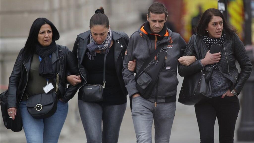 Geschokte collega's van Mickaël H. verlaten het hoofdkwartier van politie in Parijs.