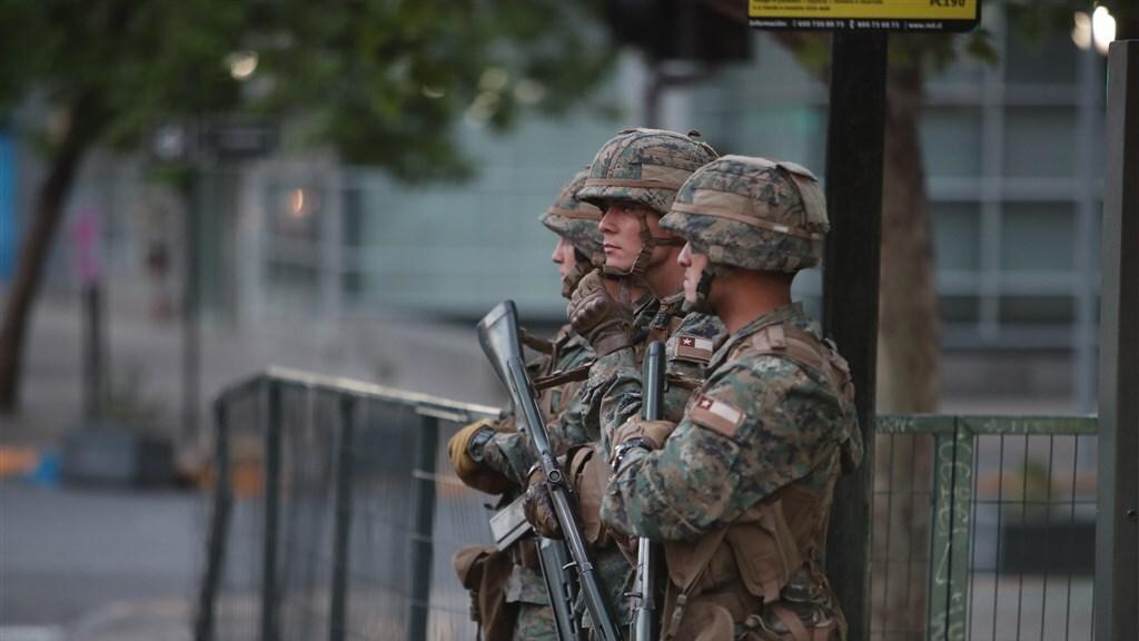 Militairen in Santiago staan klaar om in te grijpen.