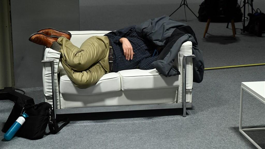 Een man slaapt tijdens de verlenging van de klimaattop in Madrid.