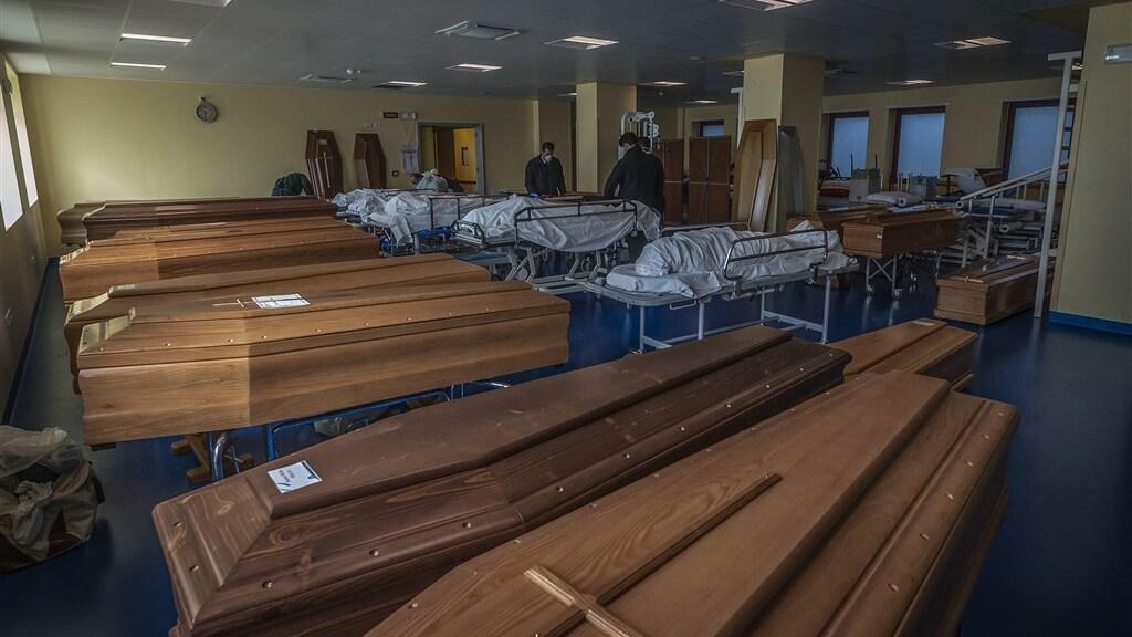 Slachtoffers van het coronavirus worden in kisten gelegd.