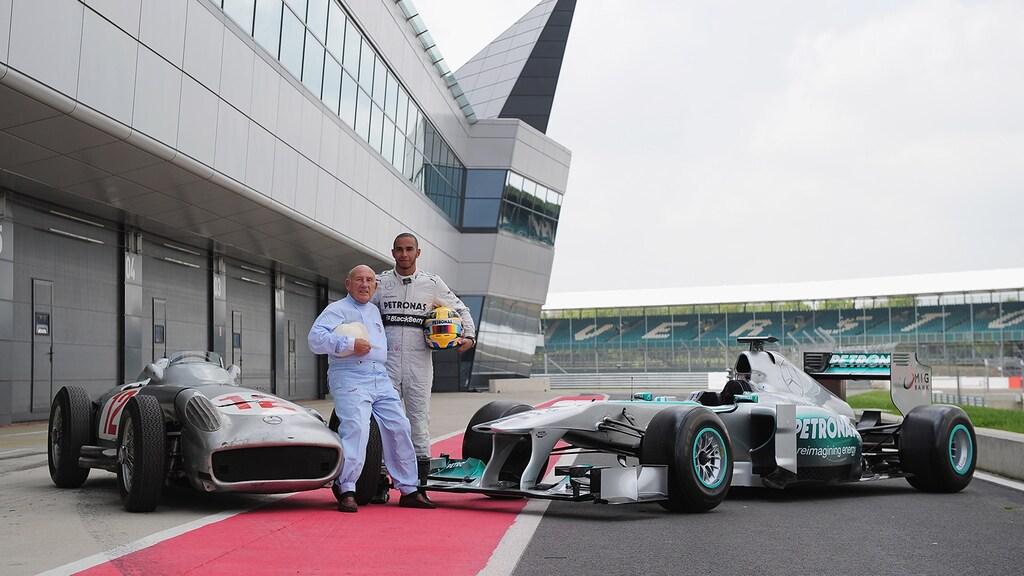 Stirling Moss en Lewis Hamilton poseren in 2013 naast hun Mercedes-bolides