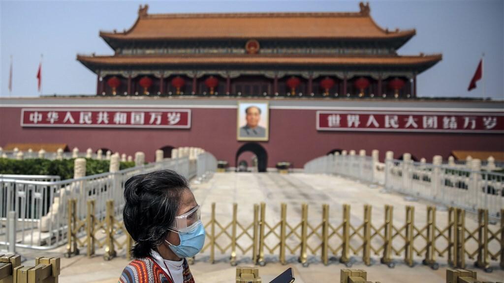 Een vrouw draagt beschermingsmiddelen op het Tiananmen Plein in Beijing.