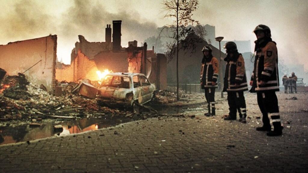 Brandweerlieden staan in de Renbaanstraat radeloos tussen de puinhopen van de verwoeste woonwijk Roombeek.