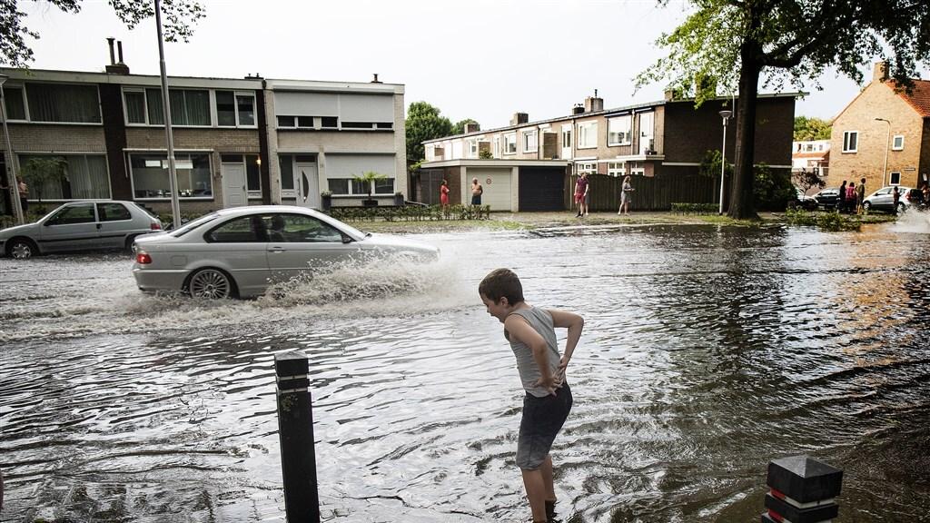 Een straat in Tilburg die is ondergelopen door de grote hoeveelheid regen.