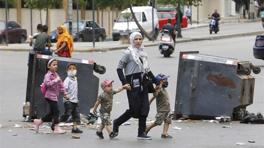 Een vrouw met kinderen loopt over straat tijdens protesten in Beiroet.