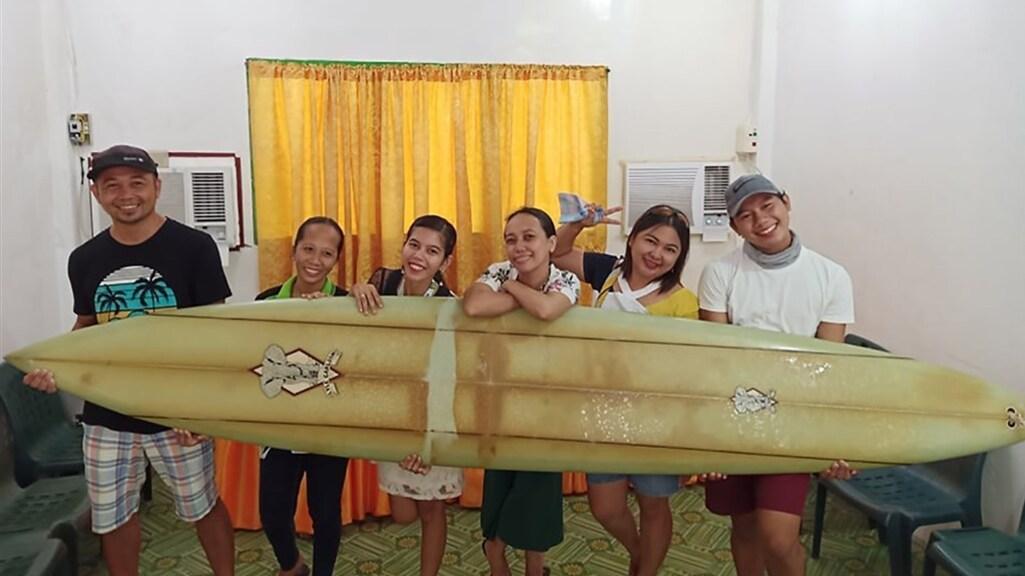 Giovanne Branzuela en zijn familie met de surfplank op de Filipijnen.