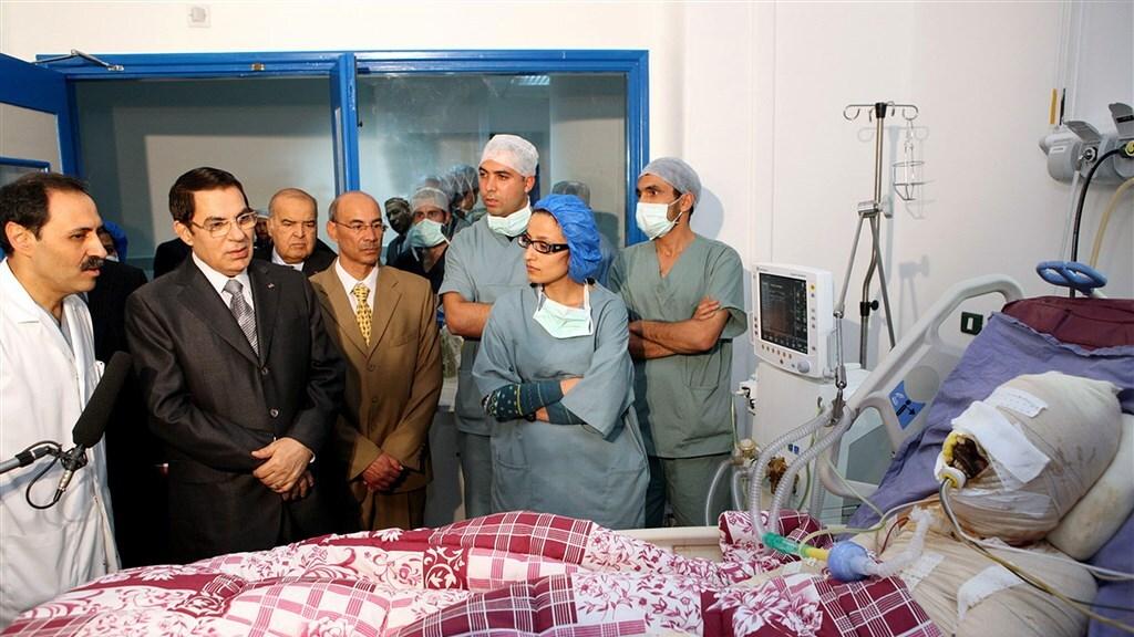 Ben Ali bezoekt de zwaargewonde Mohammed Bouazizi in het ziekenhuis.