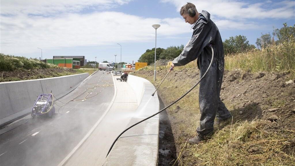 Een Poolse arbeidsmigrant spuit de muur van een viaduct schoon.