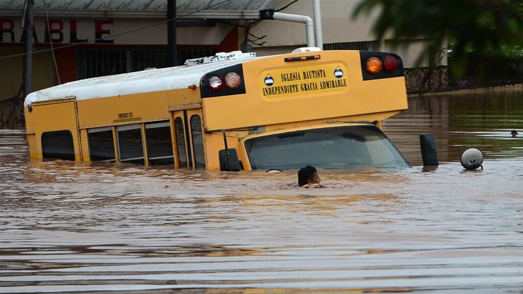 Een man zwemt langs een bus in Omonita, Honduras.