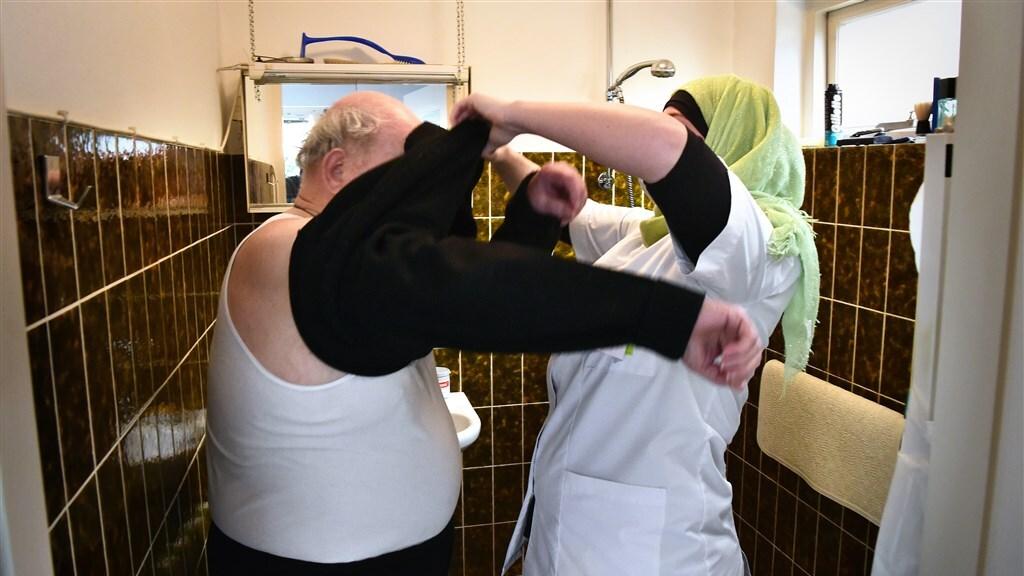 Wijkverpleegkundige helpt een oudere man met aankleden.