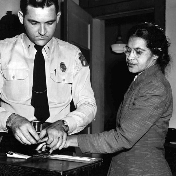 Een witte agent neemt de vingerafdruk van Rosa Parks.