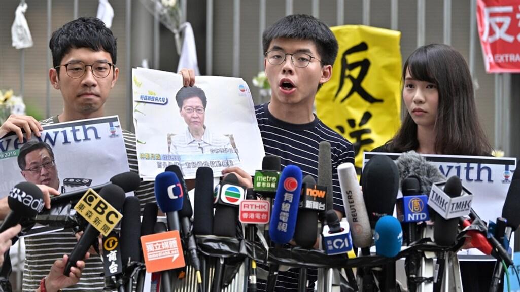 Nathan Law (links) met naast hem Joshua Wong en Agnes Chow tijdens een protest op 18 juni 2019. Law vluchtte dit jaar naar het Verenigd Koninkrijk. Zijn vrienden zitten vast.