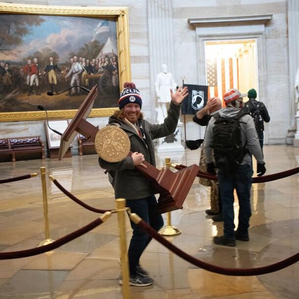 Een relschopper neemt spullen mee uit het Capitool.