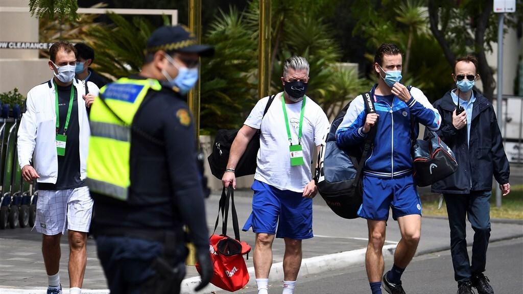 De tennissers die nog mogen trainen, worden onder strenge beveiliging naar de baan gebracht.