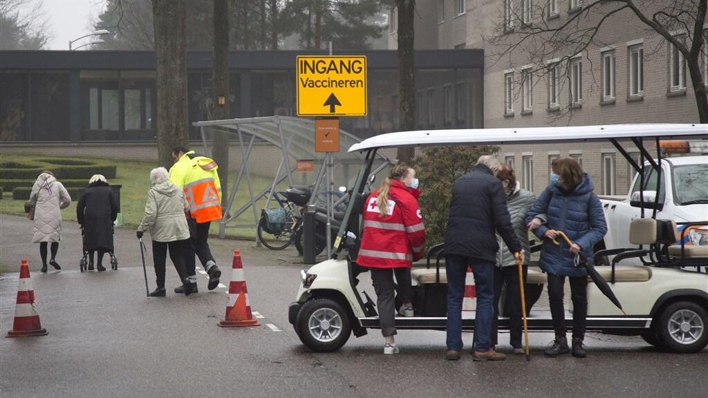 Ouderen worden na de vaccinatie in Sportcentrum Papendal teruggebracht naar de parkeerplaats met een golfkar.