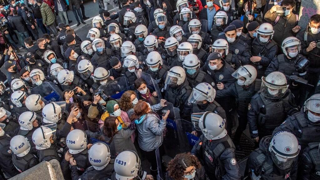 Een enorme politiemacht sluit een aantal vrouwen in.