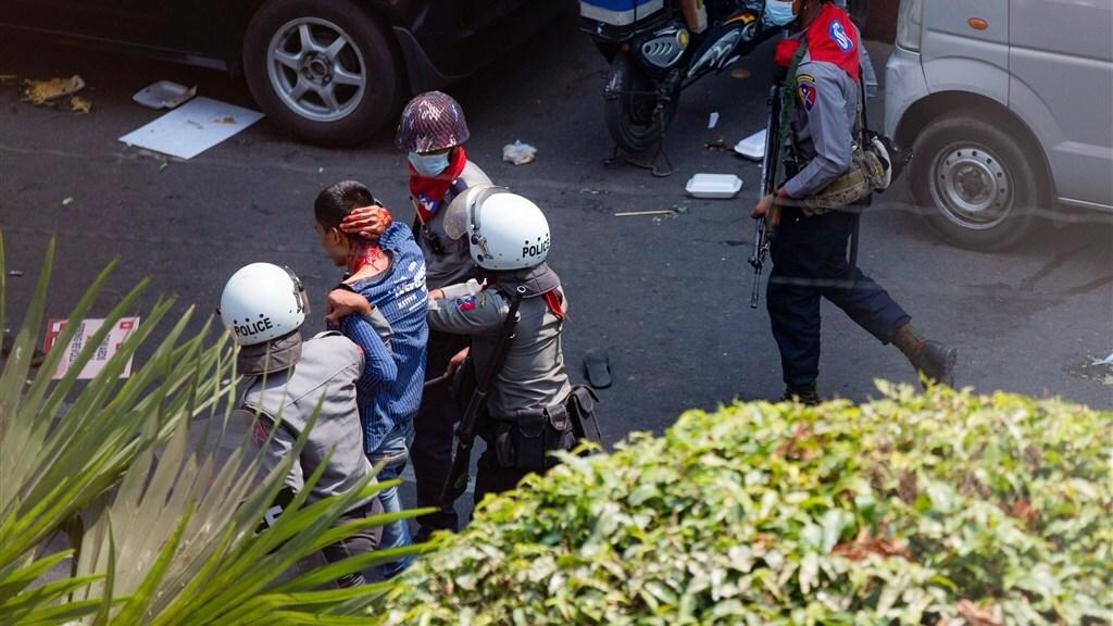 Een gewonde demonstrant wordt gearresteerd in Yangon.