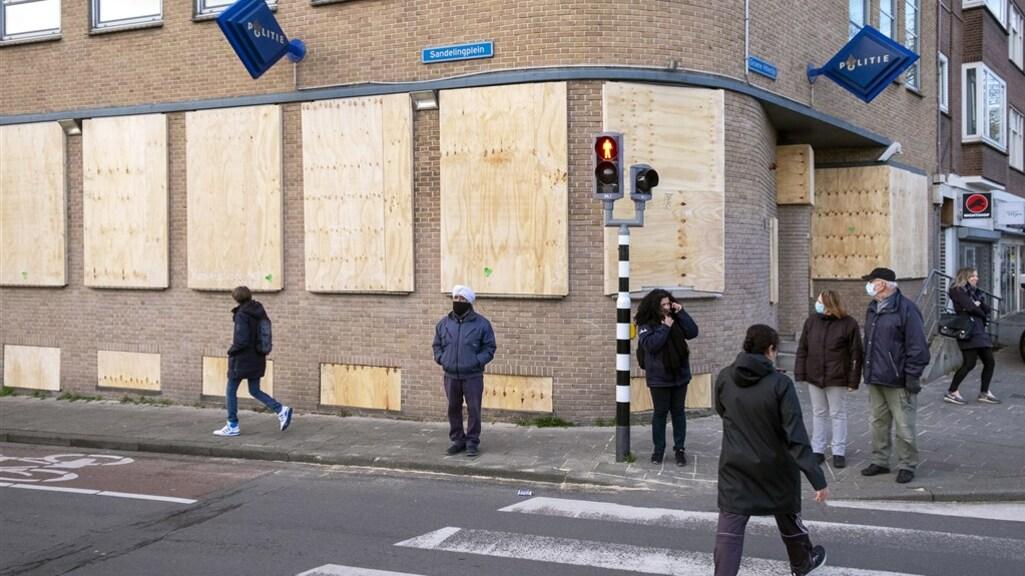 Bouwvakkers timmerden de ramen van het politiebureau aan het Sandelingenplein dicht.