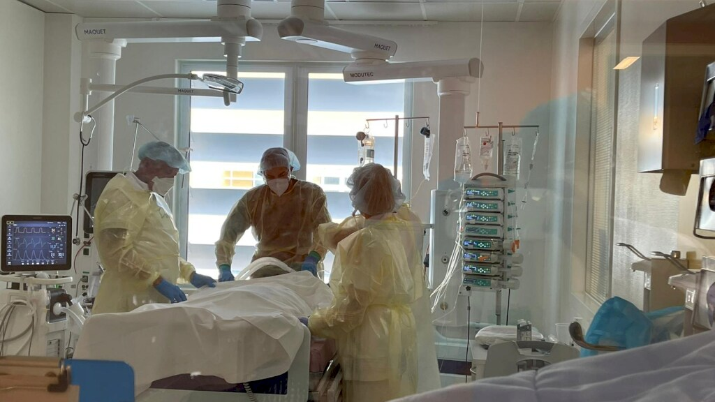 Personeel aan het bed van een coronapatiënt in het CMC.