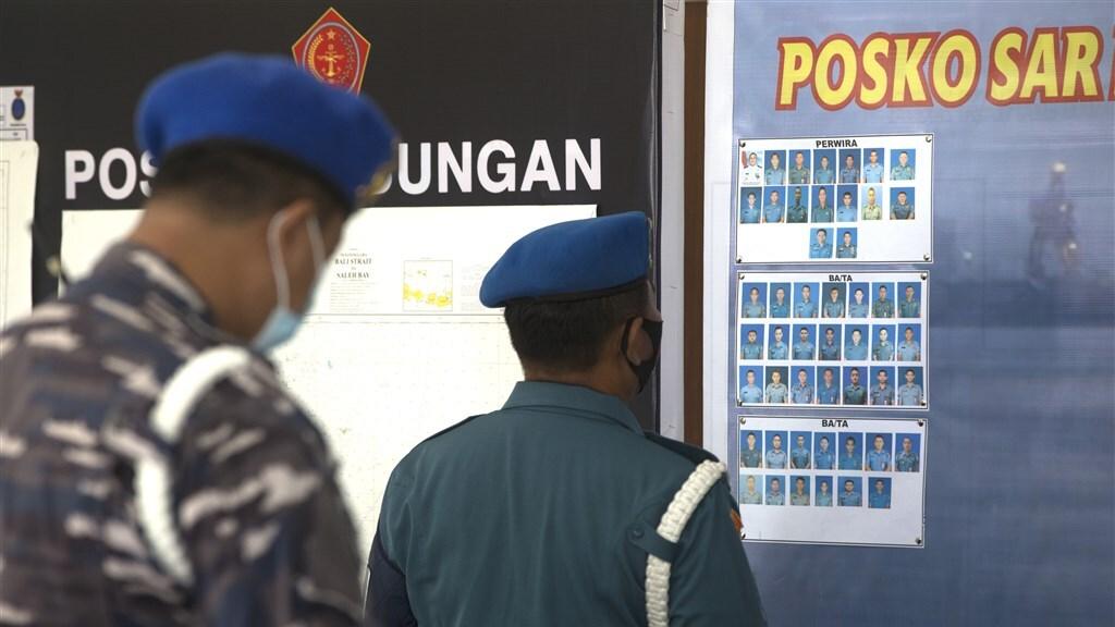 Een marine-officier kijkt naar de foto's van de bemanningsleden.