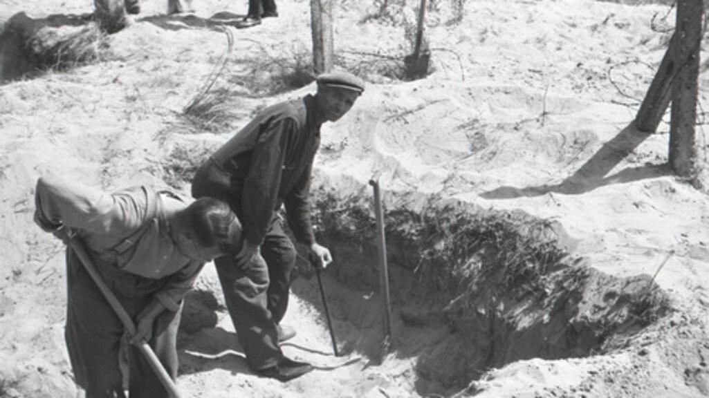 Piet Kuijt (met pet) tijdens de opgravingen van de lichamen in juli 1945.
