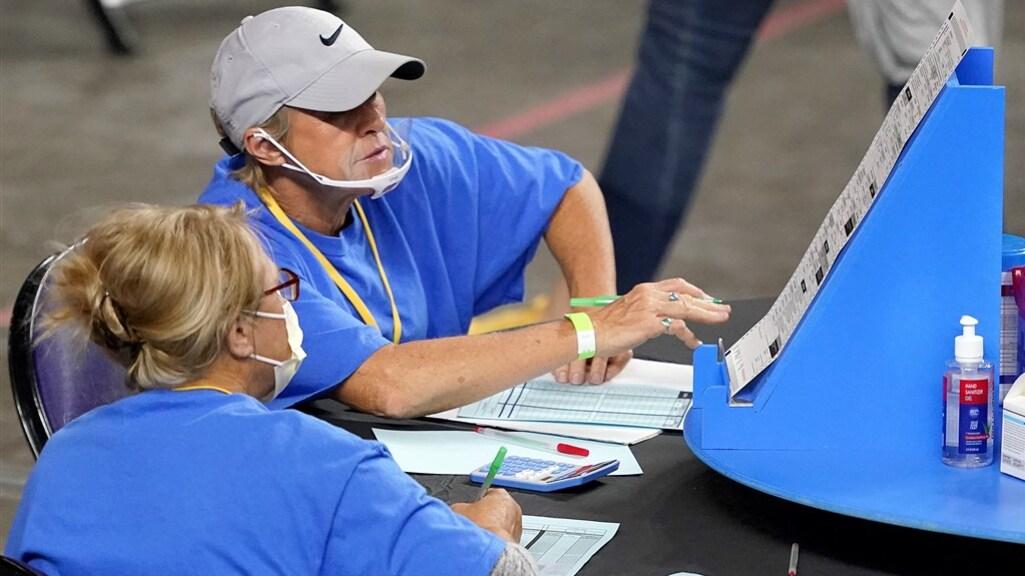 Medewerkers controleren de stembiljetten tijdens het tellen.
