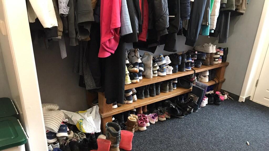 De grote gang staat vol met schoenen.