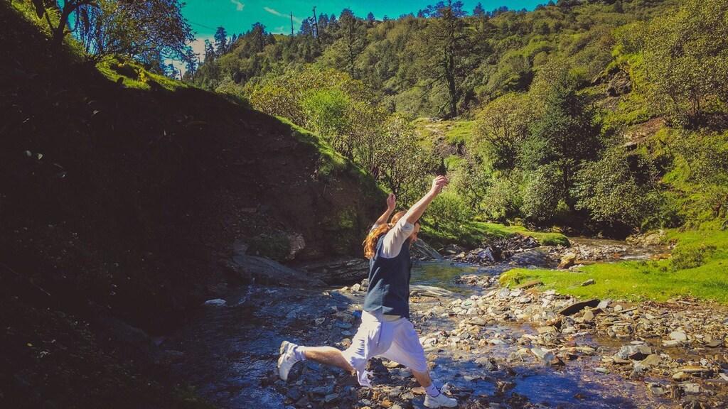 In Nepal, tijdens een wandeling in de Himalaya springt hij moeiteloos over een bergstroompje in zijn dhoti (gewaad).