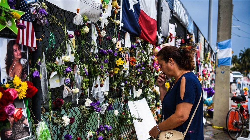 Mensen leggen bloemen bij een geïmproviseerd momument voor de slachtoffers.