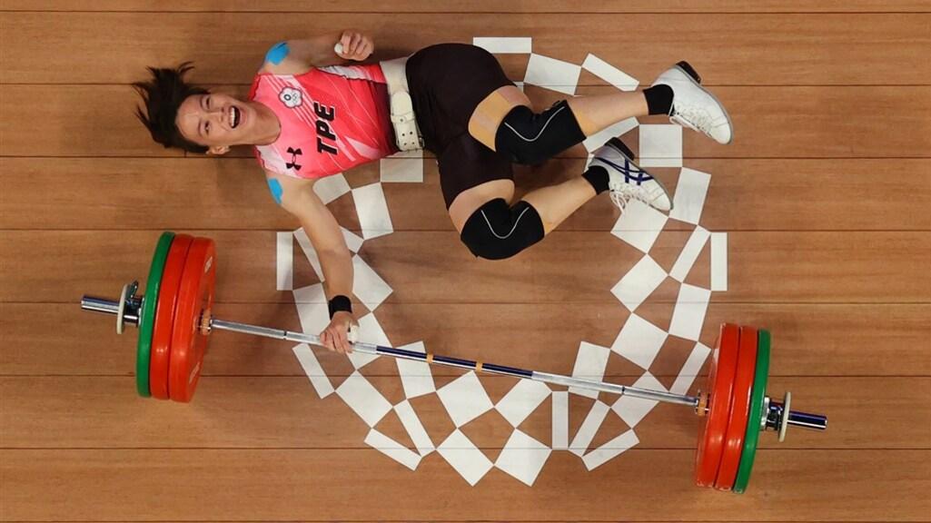De Taiwanese gewichtheffer Kuo Hsing-chun ligt op de grond na haar winnende poging waarmee ze goud won en 600.000 euro.