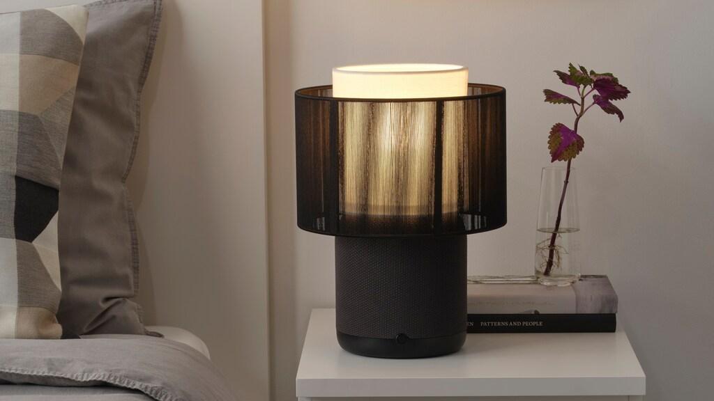 De Symfonisk-lampspeaker met zwarte, stoffen kap.