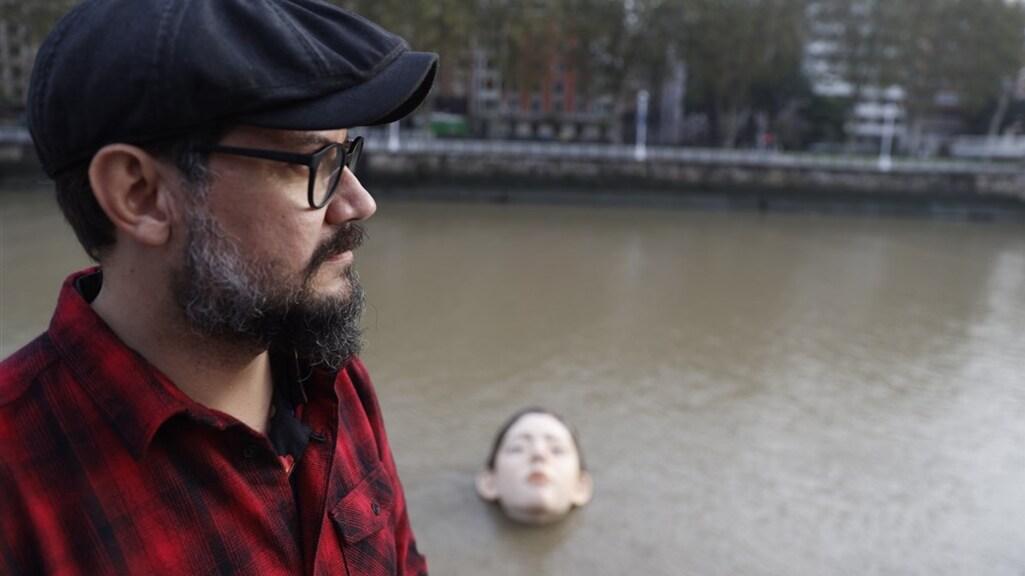 De Mexicaanse kunstenaar Ruben Orozco met op de achtergrond zijn beeld.