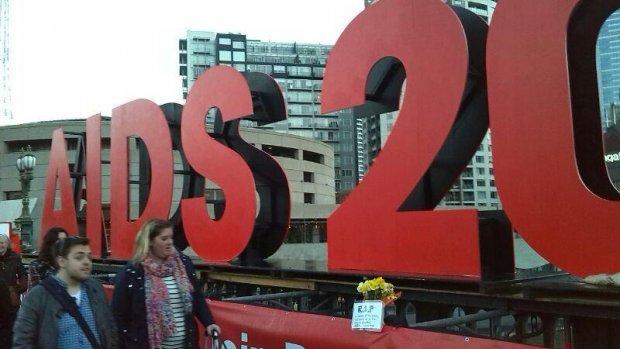 Bloemen bij bord AIDS-conferentie voor slachtoffers vliegramp