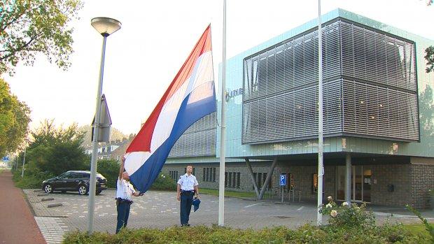 Agenten hangen vlag halfstok voor slachtoffers vliegramp