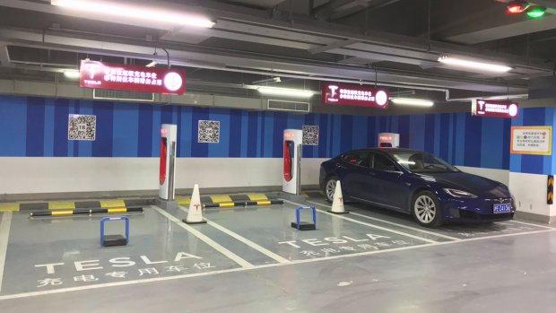Tesla-hekjes tegen benzineauto's op parkeervak met laadpaal