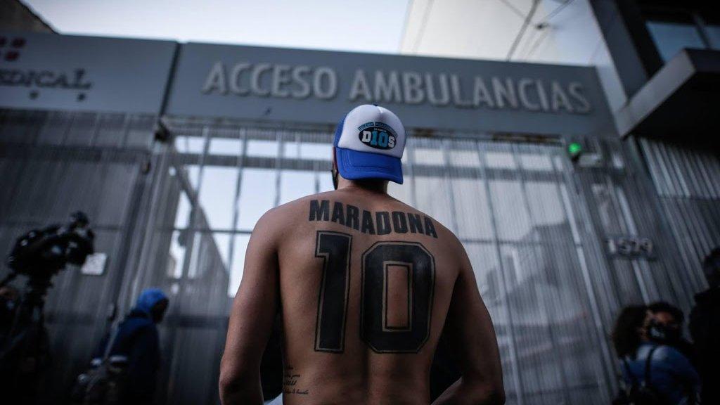 Een trouwe fan van Maradona staat buiten het ziekenhuis waar hij geopereerd is.