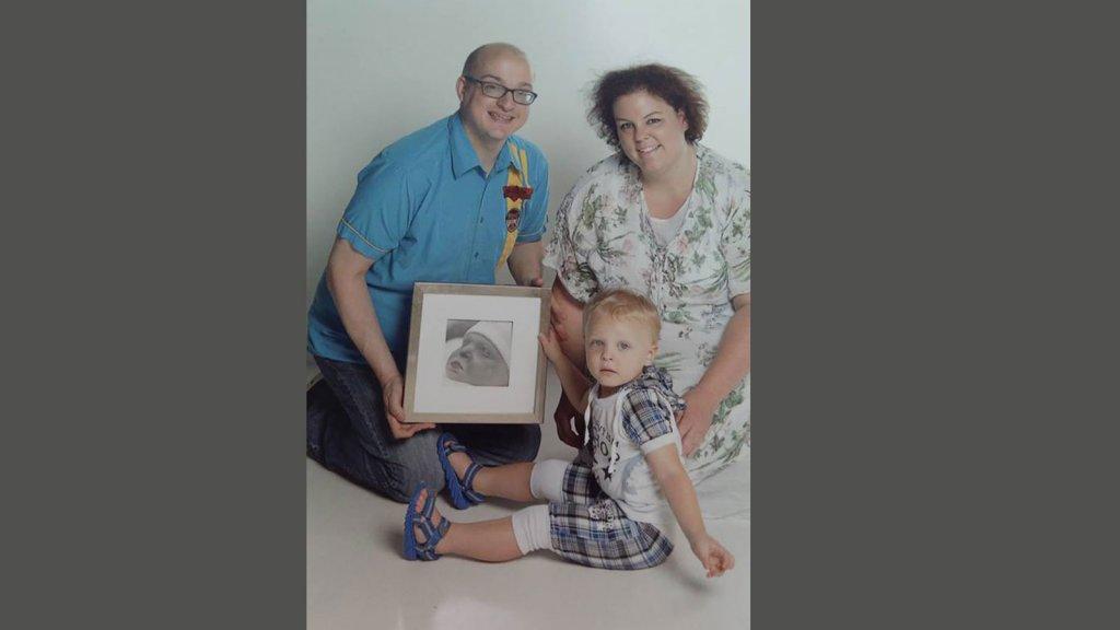 Mariska met haar man en haar zoontje en een foto van overleden dochter Tessa.