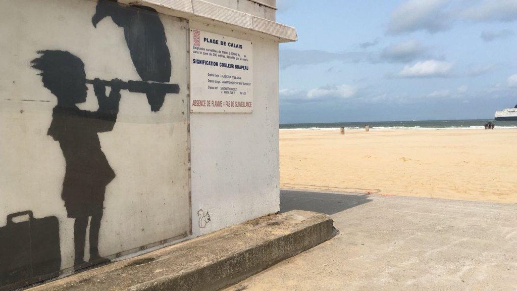 De tekening van de beroemde Britse straatartiest Banksy bij het strand van Calais.