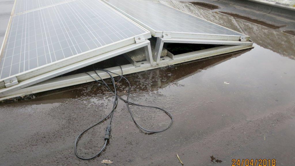 Kabels en een stekker liggen los op een dak in een plas water.